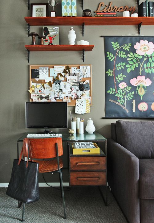 small desk with mushroom colored wall and floral illustration wall hanging