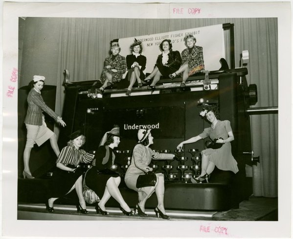 ( New York Public Library ) Nine women pose on a really big typewriter on display at the Underwood Elliott Fisher Exhibit at the New York World's Fair, 1939-40.